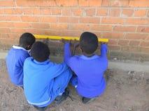 Ребеята школьного возраста измеряя размеры стены Стоковые Фотографии RF
