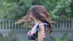 Ребяческая девушка во флористическом платье смеясь и вертясь вокруг видеоматериал