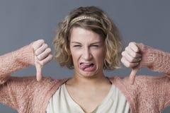 Ребяческая девушка выражая отвращение, разногласие и нелюбовь с большими пальцами руки вниз Стоковое Изображение RF