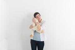 Ребяческая молодая женщина обнимая мягкого кота плюша с невиновной улыбкой и закрытыми глазами мечтает помадка Стоковое фото RF