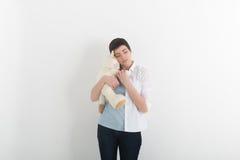 Ребяческая молодая женщина обнимая мягкую игрушку с невиновной и унылой романтичной улыбкой Стоковые Фото