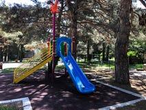 Ребяческая спортивная площадка в парке города Carousel качания в парке для детей Стоковое Изображение