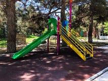 Ребяческая спортивная площадка в парке города Carousel качания в парке для детей Стоковая Фотография