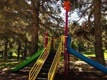 Ребяческая спортивная площадка в парке города Carousel качания в парке для детей Стоковые Фото