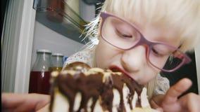 Ребяческие проказы - маленькая девочка в розовых стеклах секретно сдерживает шоколадный торт в холодильнике Любовник помадки смеш сток-видео
