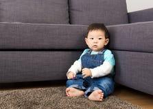 Ребёнок Азии сидя на ковре Стоковое Фото