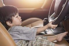 Ребёнок Азии управляя в роскошном космосе экземпляра автомобиля стоковое фото rf
