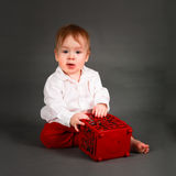 Ребёнок в белой рубашке и красных играх брюк стоковое изображение