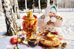 Ребёнок в пальто и головной платок в русском самоваре в ба стоковые фотографии rf