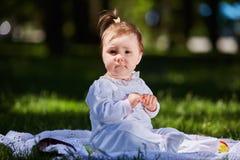 Ребёнок в платье лета сидя в зеленом луге в парке города Стоковое Фото