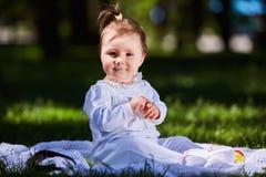 Ребёнок в платье лета сидя в зеленом луге в парке города Стоковое фото RF