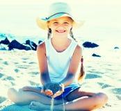 Ребёнок в шляпе играя с песком на морском побережье в лете Стоковая Фотография RF