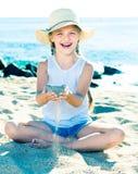 Ребёнок в шляпе играя с песком на морском побережье в лете Стоковые Изображения RF