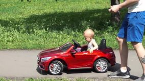 Ребёнок едет автомобиль игрушки управляемый отцом сток-видео