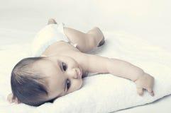 Ребёнок лежа на белом полотенце стоковое фото