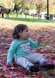 Ребёнок лежа на листьях красного цвета на осени стоковая фотография