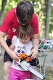 Ребёнок держа и работая с электрической пилой, цепной пилой Стоковое Фото
