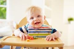Ребёнок есть плодоовощ в высоком стуле стоковое изображение rf