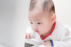 Ребёнок играя главные роли на компьтер-книжке Стоковое Изображение RF