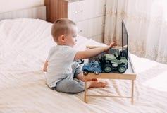ребёнок играя на компьютере или наблюдая шаржах Стоковое Изображение RF