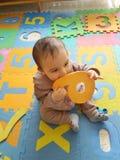 Ребёнок играя на красочном playmat Стоковые Фото
