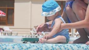 Ребёнок играя при шина игрушки сидя с мамой на бассейне, летними каникулами акции видеоматериалы