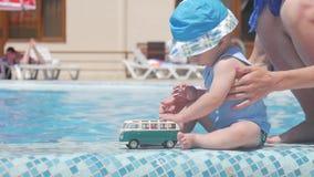 Ребёнок играя при шина игрушки сидя с мамой на бассейне, летними каникулами видеоматериал