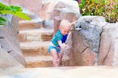 Ребёнок играя с водопроводным краном outdoors Стоковые Изображения