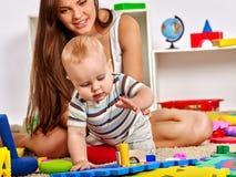 Ребёнок играя с ее молодой красивой матерью Стоковое Фото