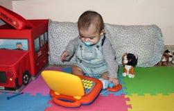 Ребёнок играя с игрушкой компьтер-книжки Стоковая Фотография
