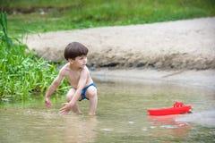 Ребёнок играя с игрушкой корабля на море Os ребенка на каникулах в лете на пляже на каникулах Стоковые Изображения