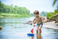 Ребёнок играя с игрушкой корабля на море Os ребенка на каникулах в лете на пляже на каникулах Стоковые Изображения RF