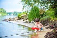 Ребёнок играя с игрушкой корабля на море Os ребенка на каникулах в лете на пляже на каникулах Стоковое Фото