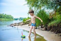 Ребёнок играя с игрушкой корабля на море Os ребенка на каникулах в лете на пляже на каникулах Стоковые Фото