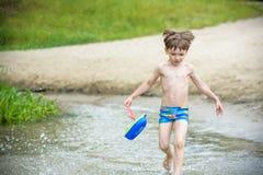 Ребёнок играя с игрушкой корабля на море Os ребенка на каникулах в лете на пляже на каникулах Стоковое Изображение