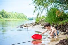 Ребёнок играя с игрушкой корабля на море Os ребенка на каникулах в лете на пляже на каникулах Стоковое Изображение RF