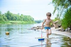Ребёнок играя с игрушкой корабля на море Os ребенка на каникулах в лете на пляже на каникулах Стоковое фото RF