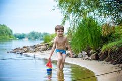 Ребёнок играя с игрушкой корабля на море Os ребенка на каникулах в лете на пляже на каникулах Стоковые Фотографии RF