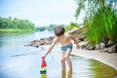 Ребёнок играя с игрушкой корабля на море Os ребенка на каникулах в s Стоковое фото RF