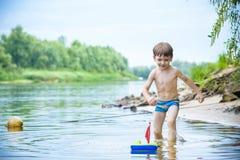 Ребёнок играя с игрушкой корабля на море Os ребенка на каникулах в s Стоковые Фотографии RF
