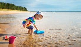 Ребёнок играя с игрушкой корабля на море Стоковая Фотография RF