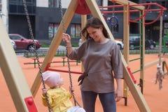 Ребёнок имея потеху на качании стоковое фото rf