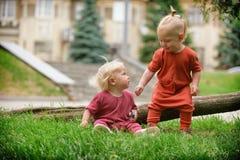 Ребёнок и ребёнок играя пока сидящ на зеленой траве Стоковая Фотография