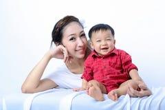 Ребёнок и мать портрета азиатские усмехающся и смеющся над дальше Стоковое фото RF