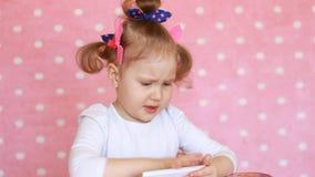 Ребёнок касается пальцу сенсорный экран smartphone и нагружается применения акции видеоматериалы
