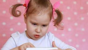 Ребёнок касается пальцу сенсорный экран smartphone и нагружается применения видеоматериал