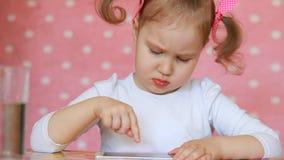 Ребёнок касается пальцу сенсорный экран smartphone и нагружается применения сток-видео
