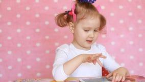 Ребёнок касается сенсорному экрану smartphone и нагружается применения видеоматериал