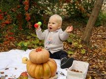 Ребёнок 1 лет старый, представляющ с тыквой и игрушками среди деревьев i Стоковое Изображение RF