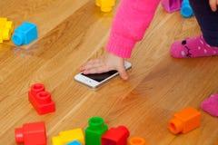 Ребёнок малыша играя с умным телефоном между игрушками Стоковое фото RF